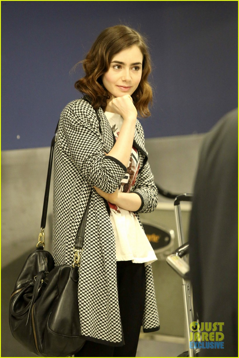 lily collins pushes giant luggage cart after mortals tour 022939603