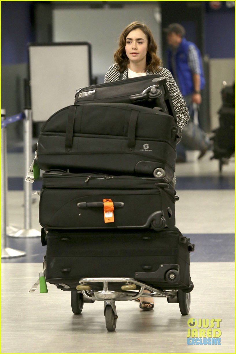 lily collins pushes giant luggage cart after mortals tour 062939607