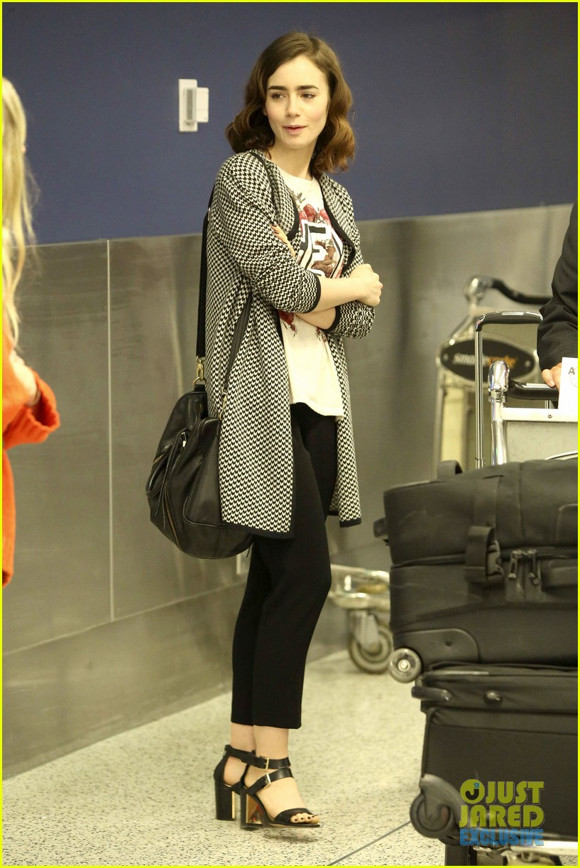 lily collins pushes giant luggage cart after mortals tour 082939609