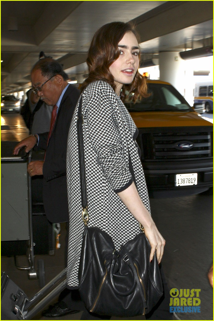 lily collins pushes giant luggage cart after mortals tour 102939611