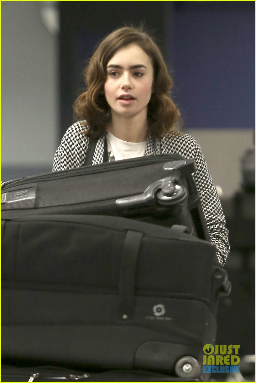 lily collins pushes giant luggage cart after mortals tour 112939612