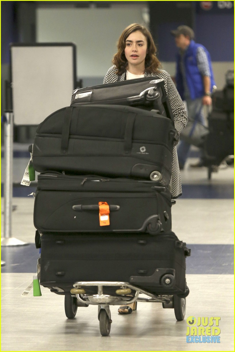 lily collins pushes giant luggage cart after mortals tour 122939613