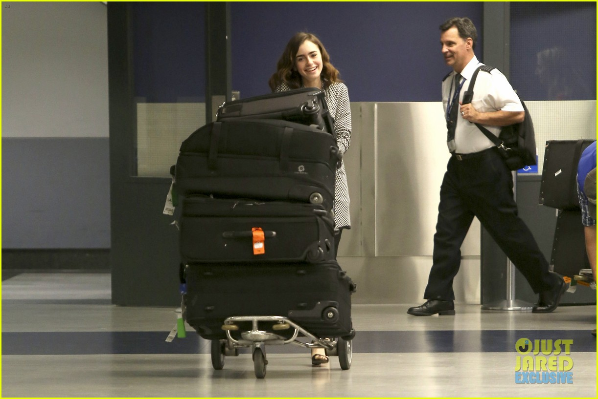 lily collins pushes giant luggage cart after mortals tour 162939617