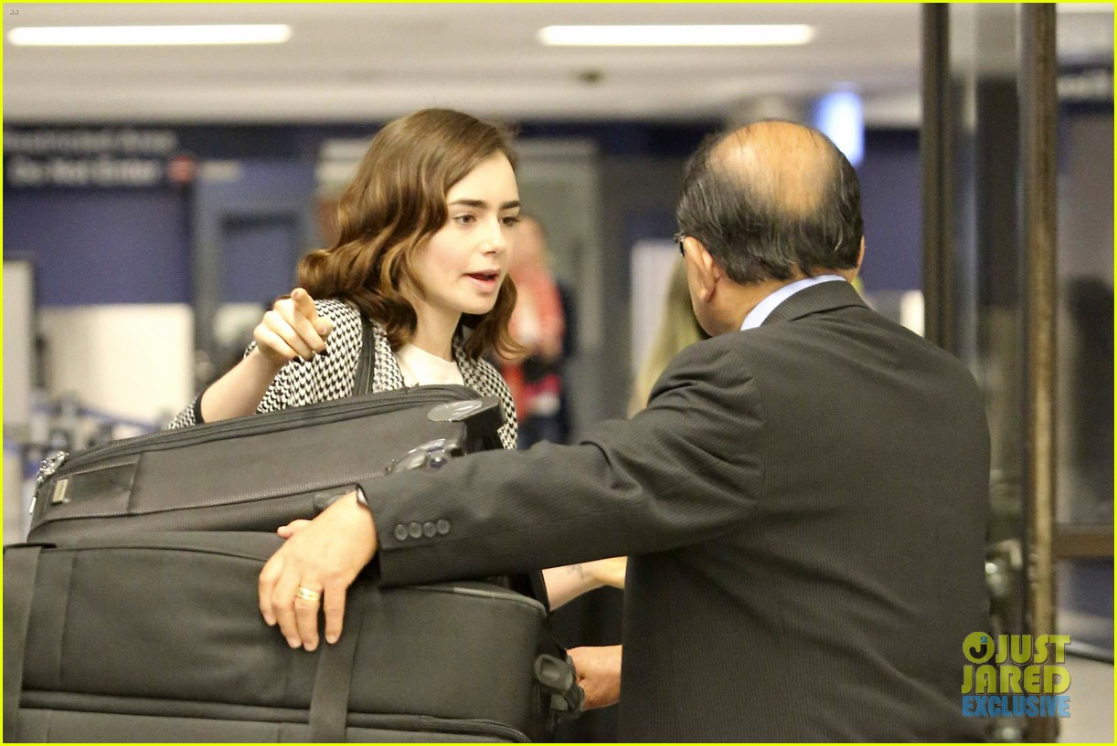 lily collins pushes giant luggage cart after mortals tour 182939619