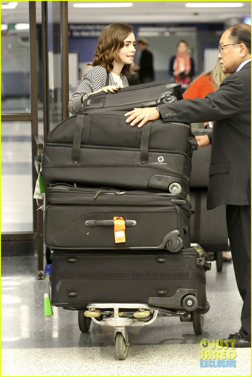 lily collins pushes giant luggage cart after mortals tour 192939620