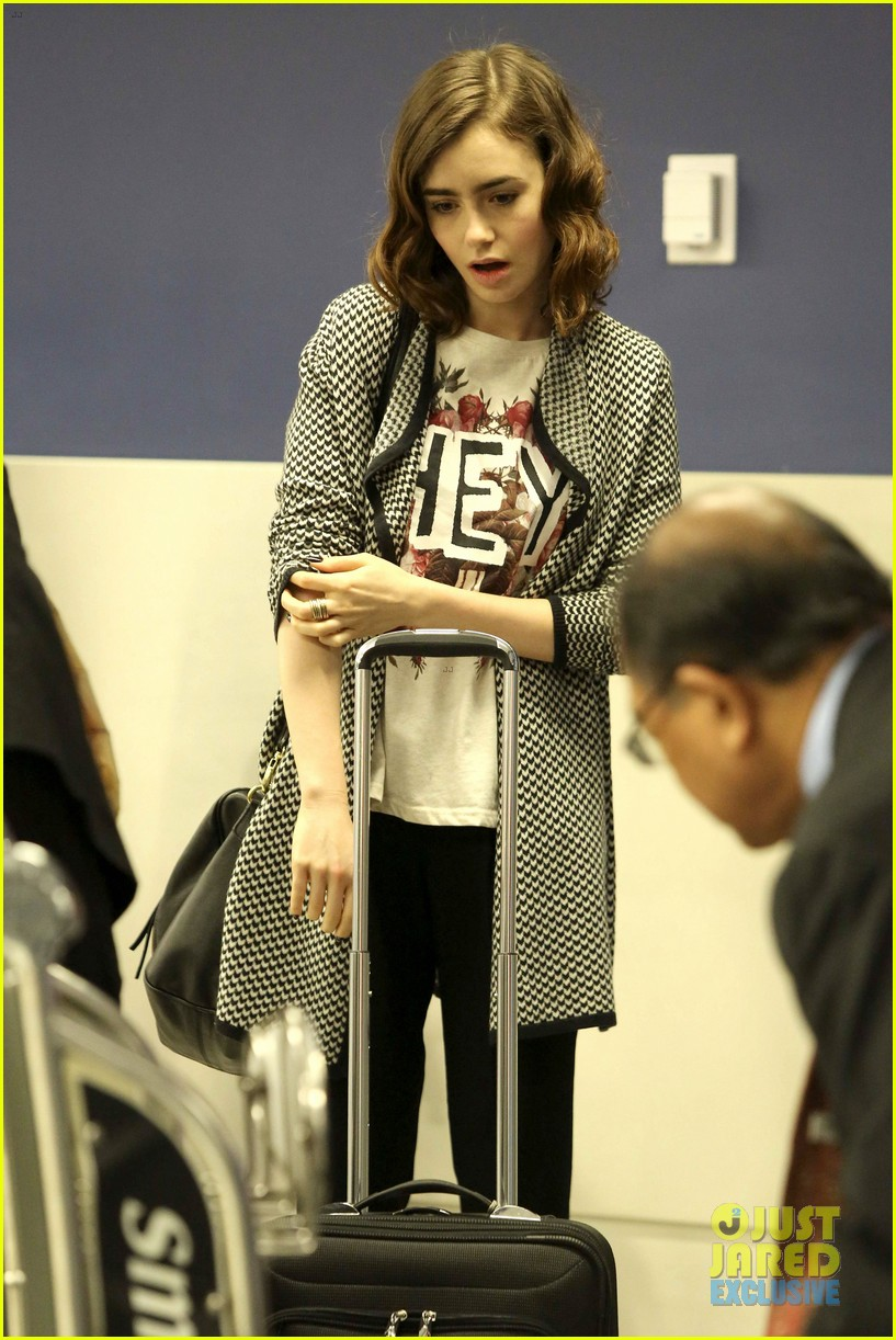 lily collins pushes giant luggage cart after mortals tour 202939621