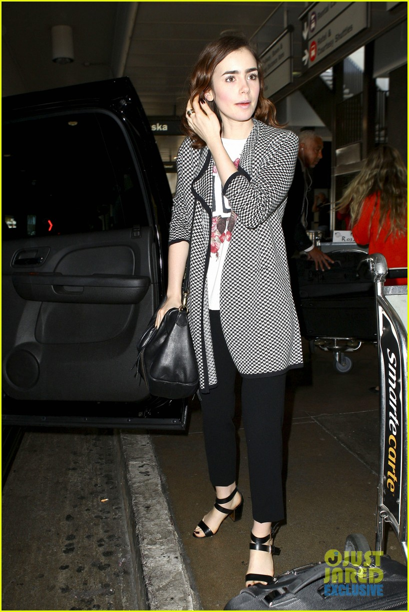 lily collins pushes giant luggage cart after mortals tour 242939625