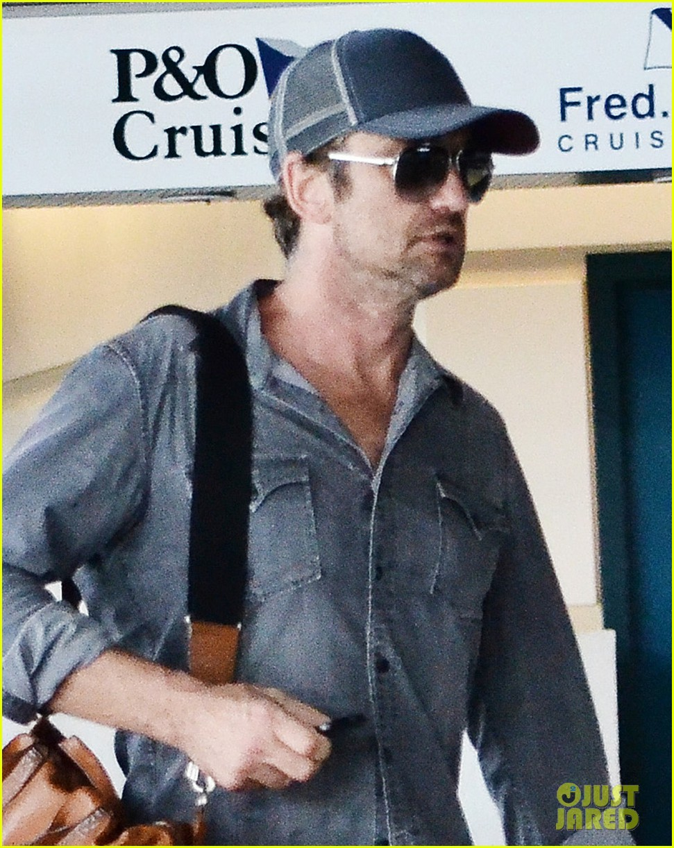 gerard butler ducks under ropes at barbados airport 022941831