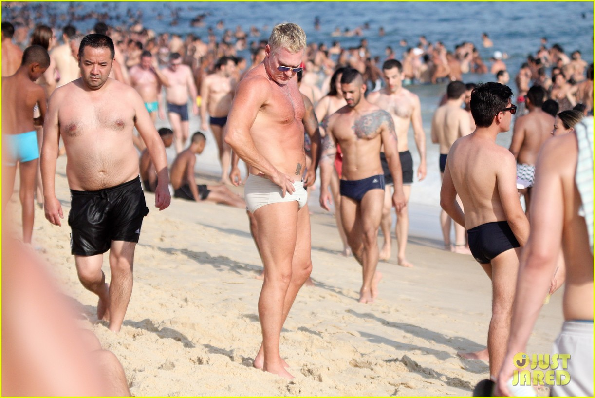 sam champion strips off board shorts to show speedo 30