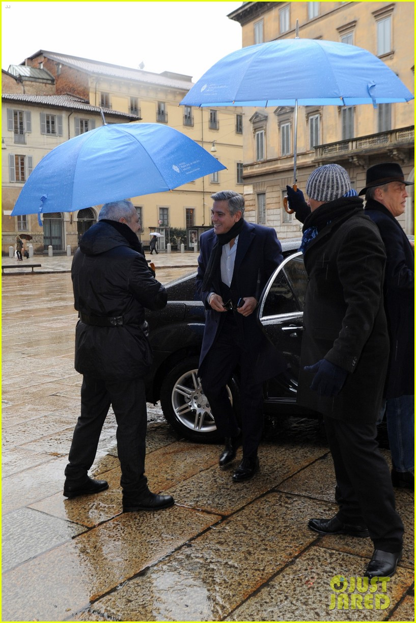 matt damon george clooney get personal umbrella holders in milan 083050716