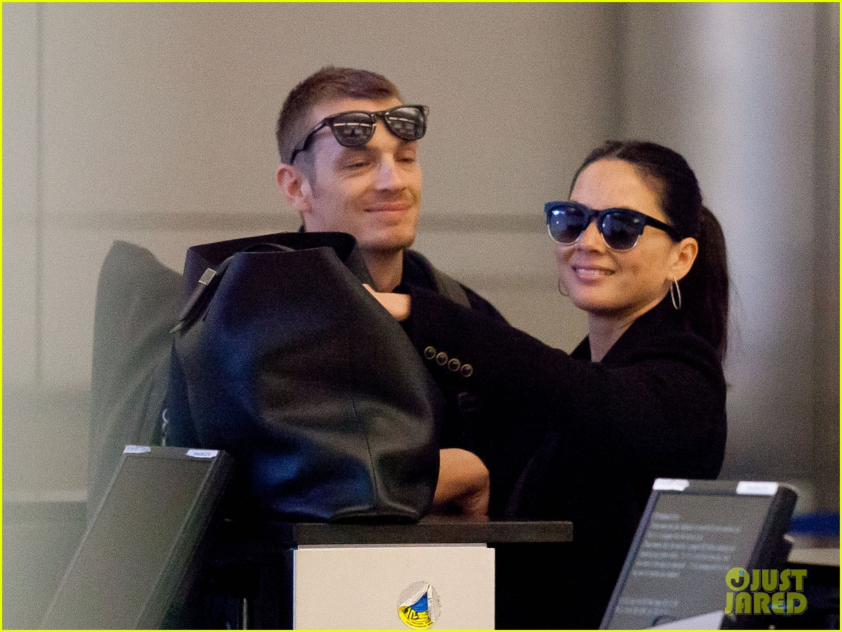 joel kinnaman sneaks in a kiss with olivia munn at lax 01