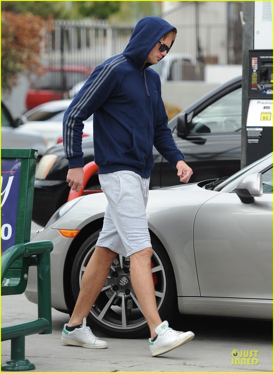 alexander skarsgard hides under a hoodie at gas station 10