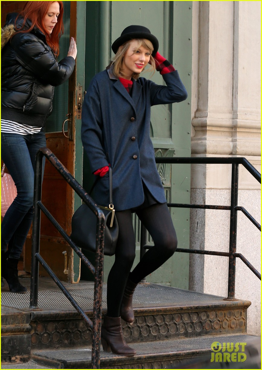 taylor swift holds onto her hat before it flies off her head 033078948
