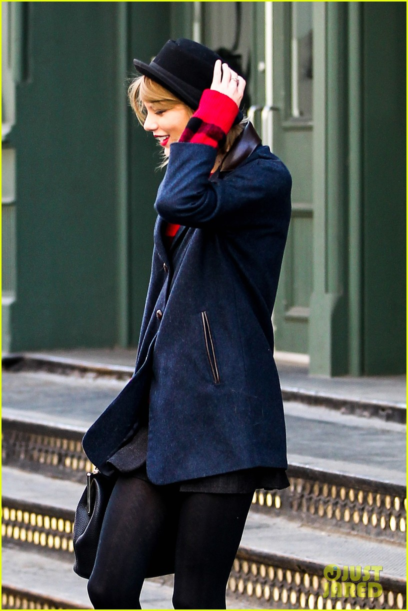taylor swift holds onto her hat before it flies off her head 043078949