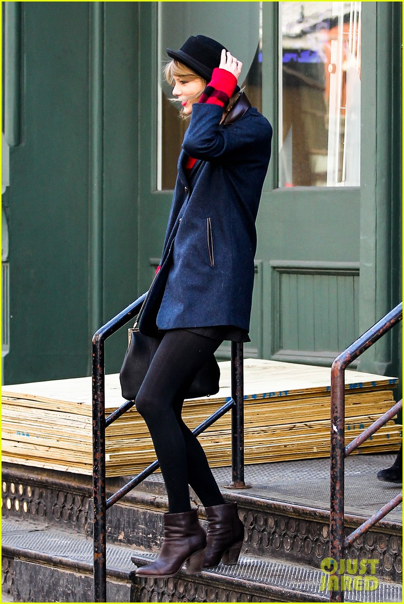 taylor swift holds onto her hat before it flies off her head 053078950