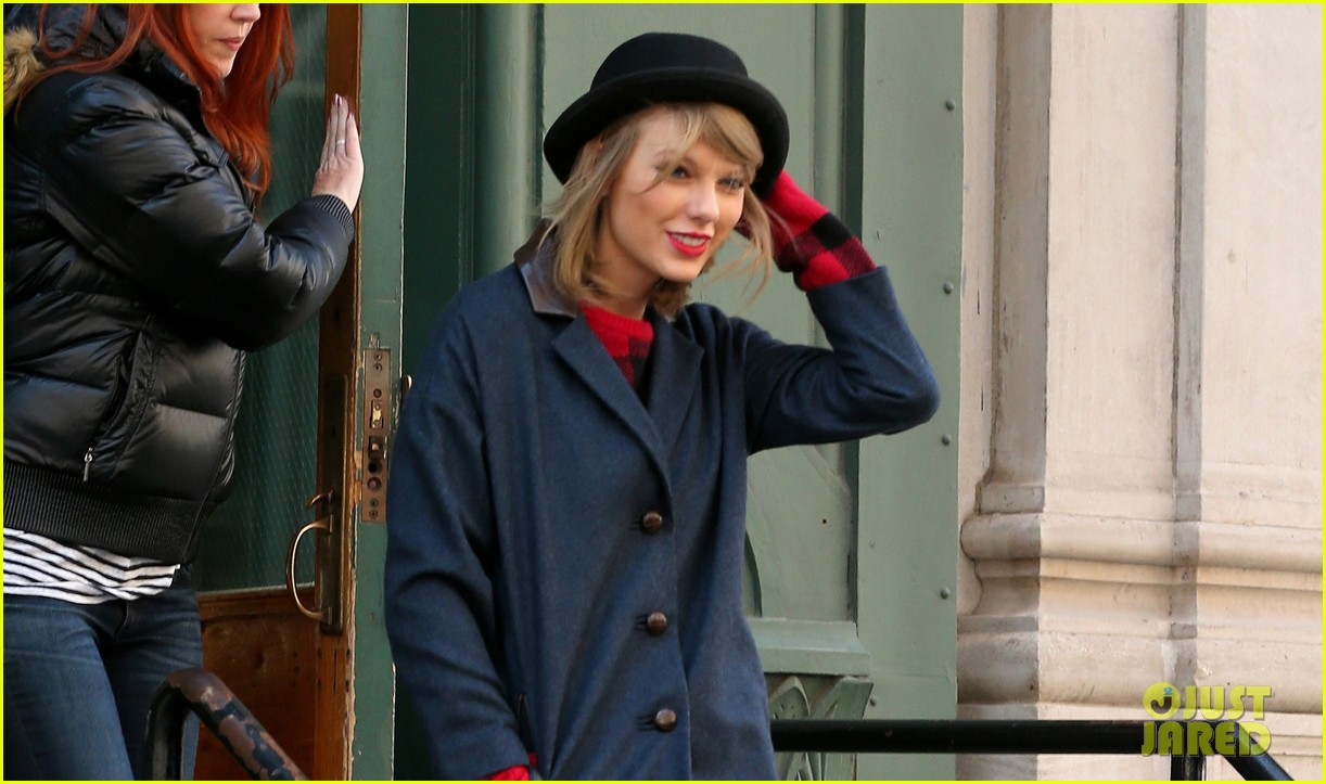 taylor swift holds onto her hat before it flies off her head 103078955