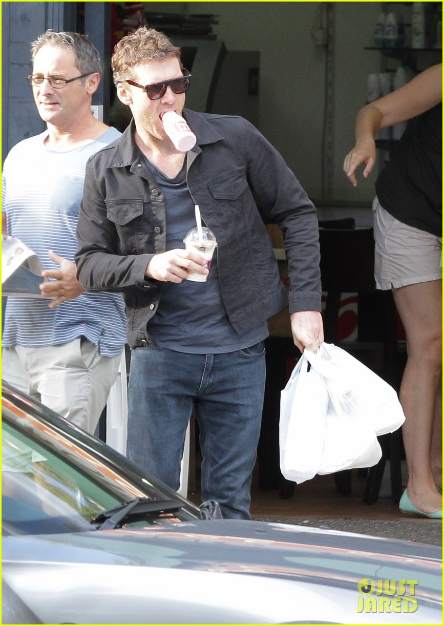 sam worthington juggles bags beverages in sydney 09