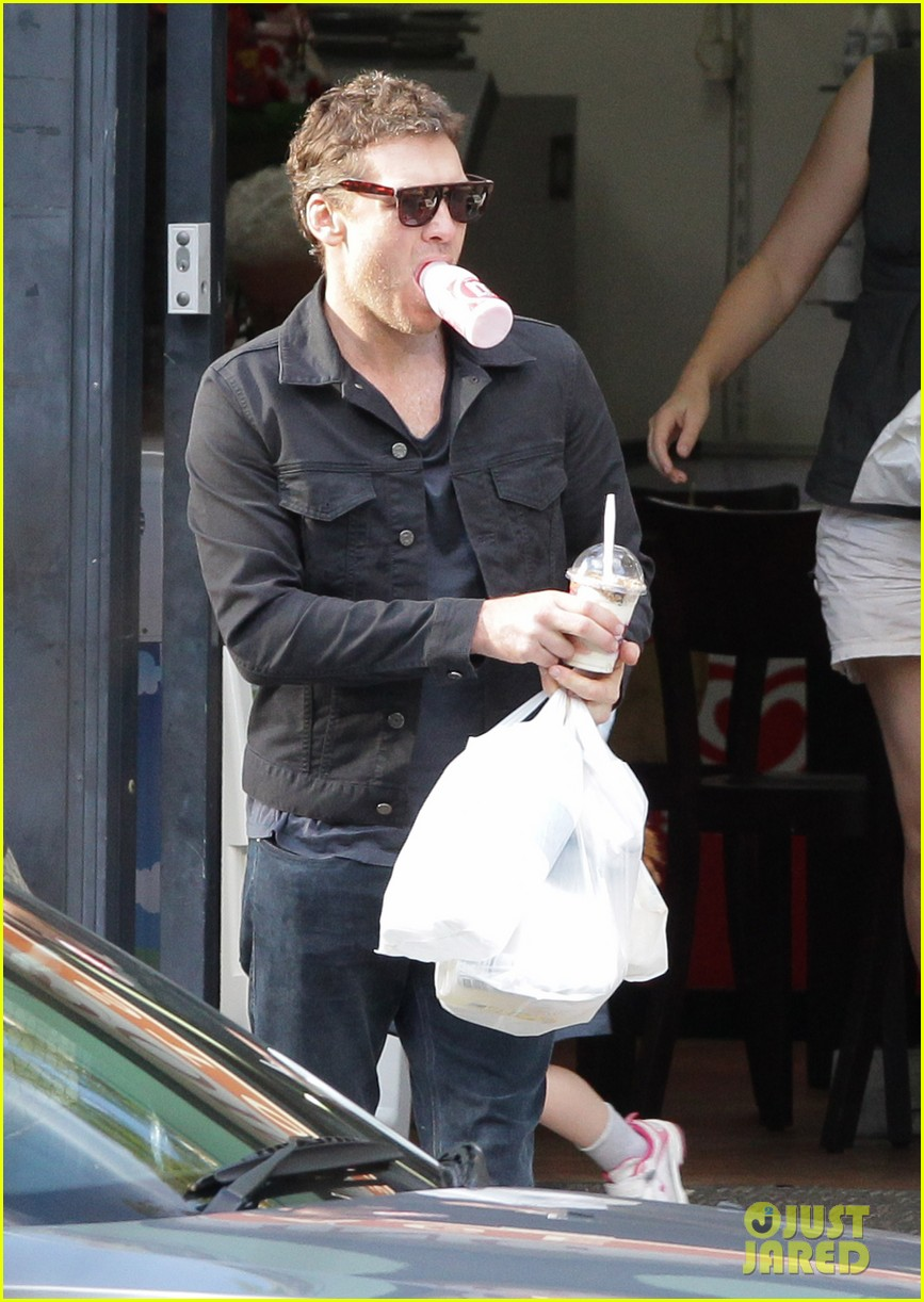 sam worthington juggles bags beverages in sydney 11