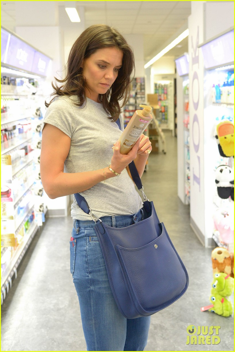 katie holmes intensly examines a bottle of tanning moisturizer 013129134