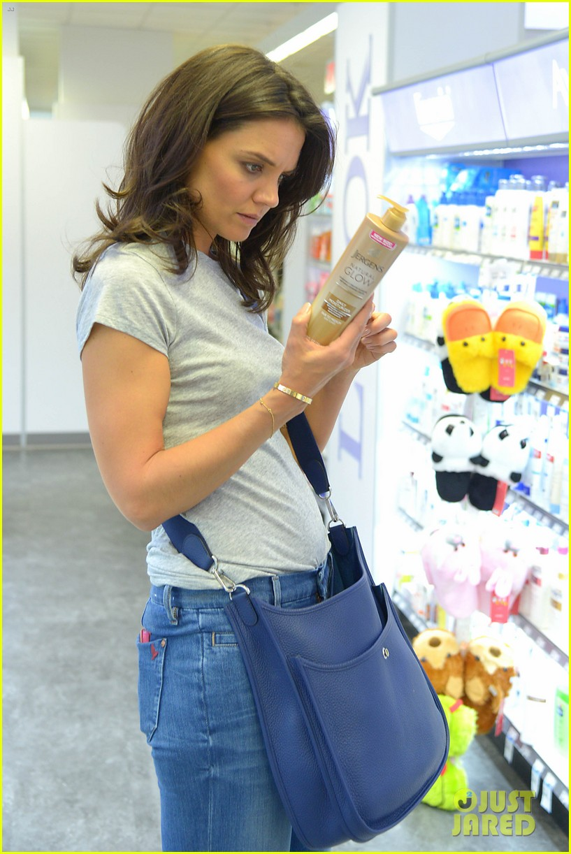 katie holmes intensly examines a bottle of tanning moisturizer 033129136