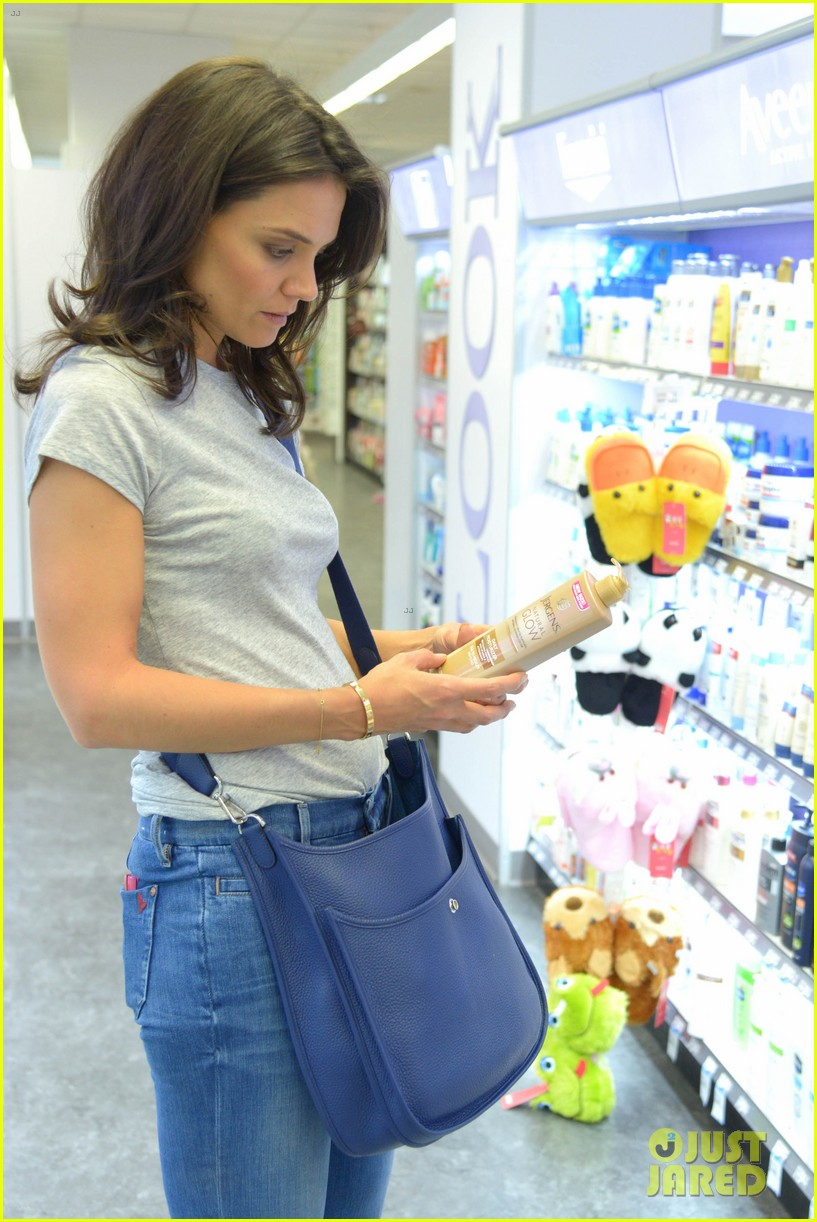 katie holmes intensly examines a bottle of tanning moisturizer 043129137
