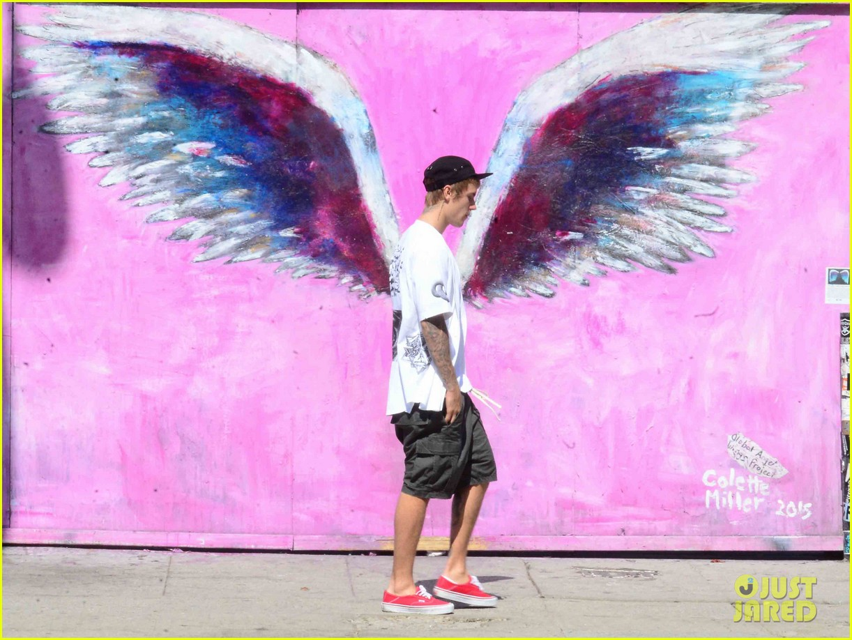 justin bieber walks by wings wall portrait at perfect time 033967253