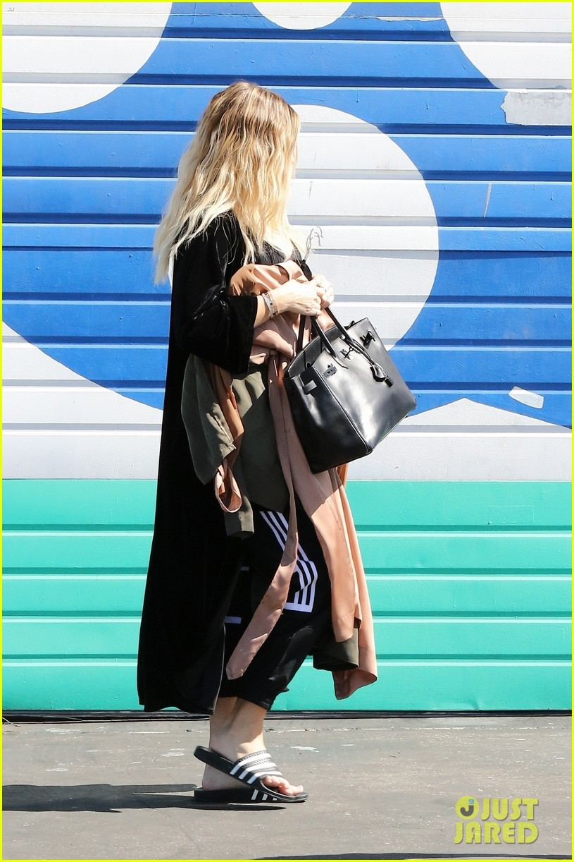 khloe kardashian holds clothes over baby bump to cover up 033970670