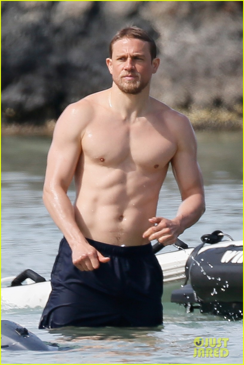 shirtless charlie hunnam puts on sunscreen at the beach in