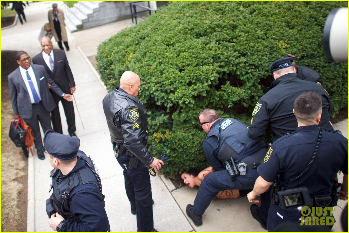 Topless protester launches herself at Bill Cosby outside