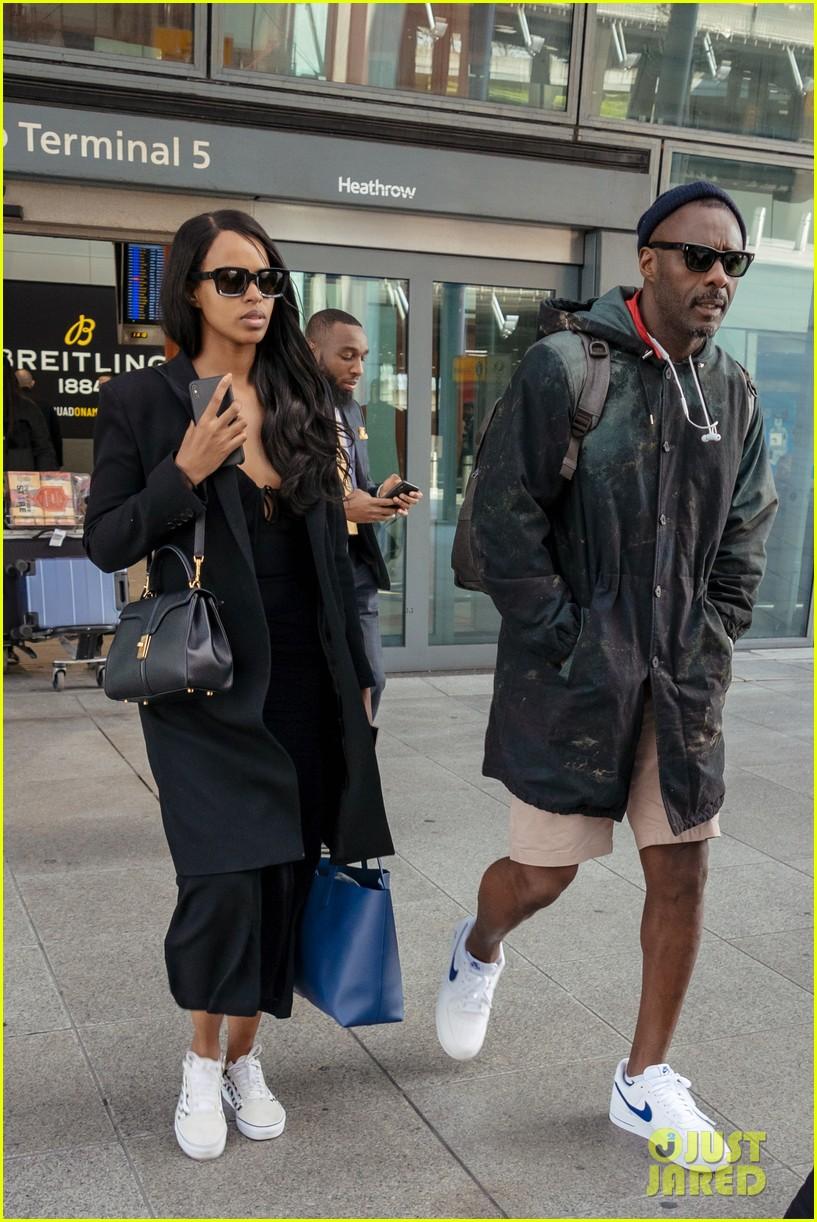 idris elba and fiancee sabrina dhowre land in london after coachella 01