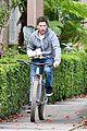 christian bale balances tray of coffees while riding a bike 01