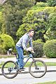 christian bale balances tray of coffees while riding a bike 05