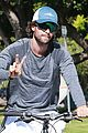 patrick schwarzenegger throws up peace on a bike ride 02