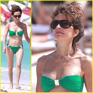 With her petite body and Regular brown hairtype without bra (cup size ) on the beach in bikini