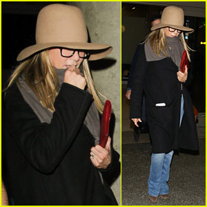Jennifer Aniston Covers Up While Arriving Back in LA