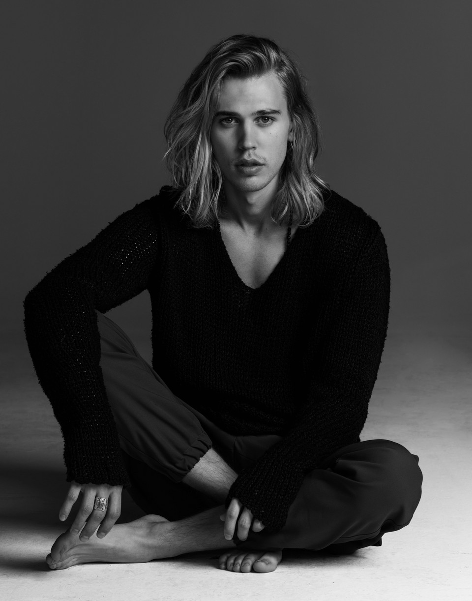 Austin Butler sitting on the ground while barefoot