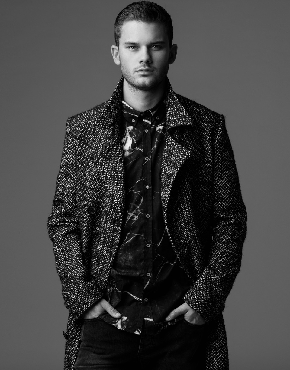 Jeremy Irvine standing with hands in his pockets